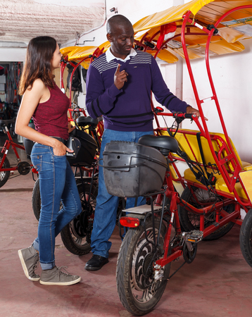 Young positive woman planning to hire rickshaw, negotiating with Afro-American driver