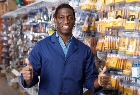 Adult African American seller of household store standing near racks with goods, giving thumbs up