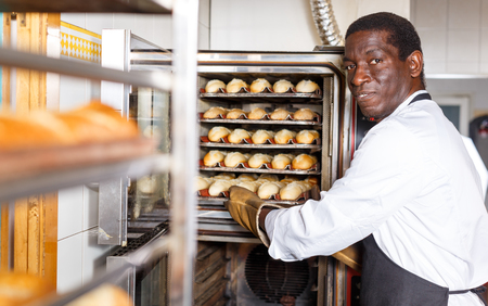Experienced baker working in small bakery, taking out bread from industrial oven 版權商用圖片