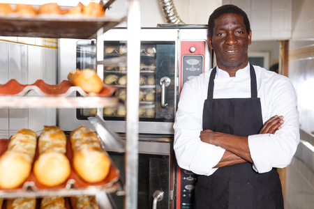 Confident baker in black apron standing with arms crossed near professional bread oven in small bakery