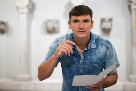 Young man with information booklet in his hands looking at exhibits in historical museum