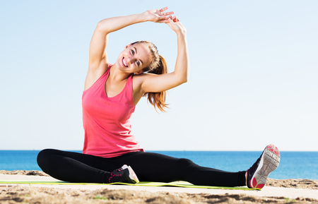 Young positive girl doing yoga at seaside on a sunny day