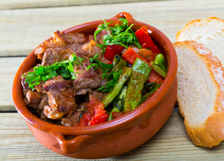 Bulgarian cuisine. Gyuvech - baked meat and vegetable stew served with greens in clay pot