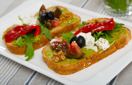 Healthy toasts with guacamole, fresh vegetables, feta cheese and walnut served on white plate