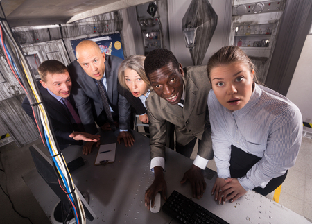 Portrait of group of thoughtful people in business suits at escape room Banco de Imagens