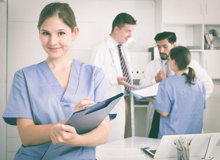 Junger Doktorassistent, der im Ärztlichen Dienst merkt Verordnungen steht