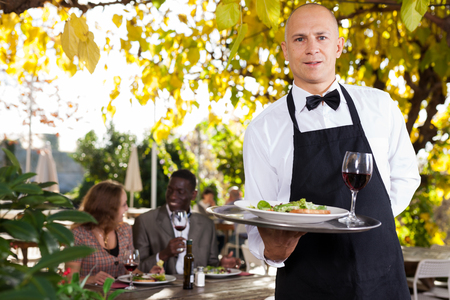 Adult waiter who is standing with order at summer cafe Stock fotó - 117169106