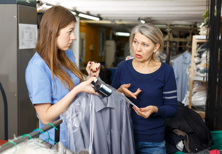 Female client complaining about cost of service at dry-cleaning salon