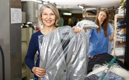 Woman holding her clean clothes in plastic bags at dry-cleaning salon