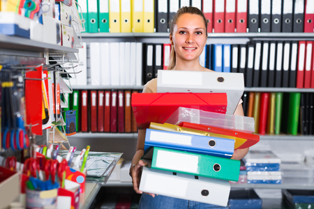Smiling woman is staying with folders in stationery shop.
