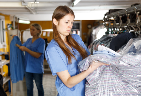 Two female dry-cleaning salon workers inspecting clothes after cleaning