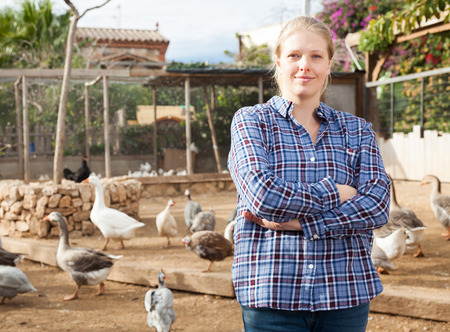 Portrait of smiling and confident young female farmer on poultry yard on background with domestic fowl