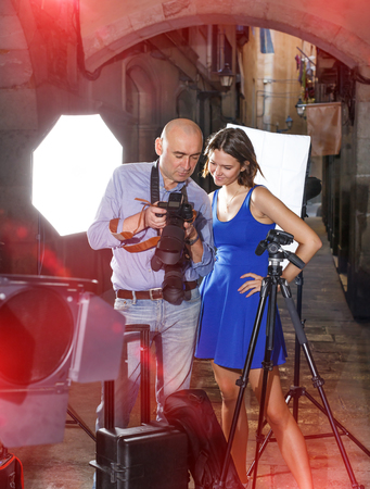 Professional photographer showing photos on a digital camera to smiling model girl during shooting at the old city street Stock Photo