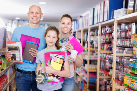 Family with daughter schoolgirl holding school accessories in store of stationery