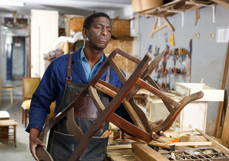 Portrait of craftsman restoring old chair in woodwork studio