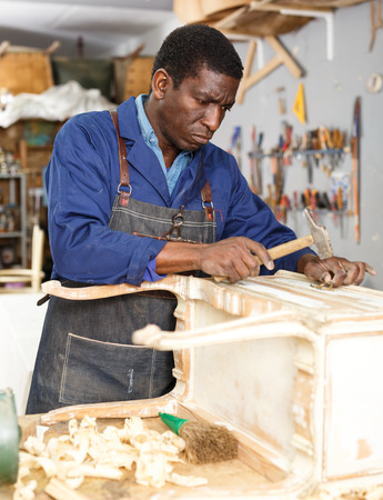 Professional furniture restorer renewing vintage chest of drawers in workshop