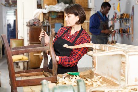 Professional female furniture restorer inspecting vintage armchair in workshop