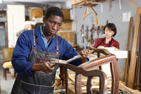Portrait of craftsman restoring old chair in woodwork studio