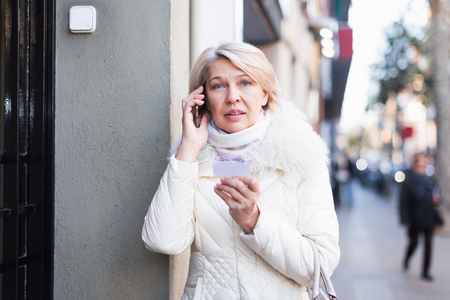 Woman talking on phone near door and holding paper with address