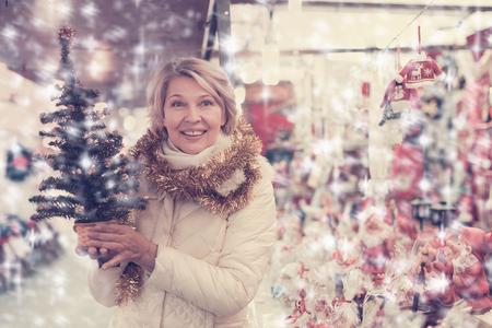 Portrait of mature female in tinsel choosing Christmas tree at fair