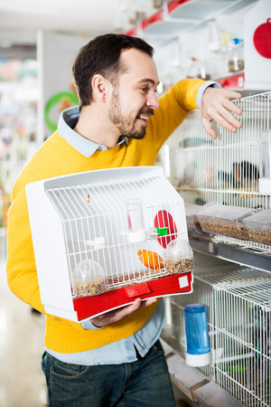 Adult handsome man choosing pretty bird for keeping in pet shop 写真素材