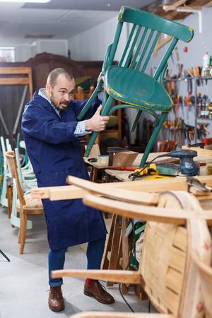 Professional furniture restorer inspecting vintage armchair in workshop