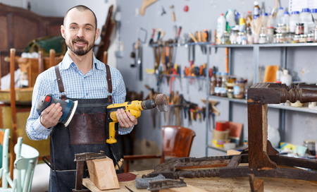Cheerful craftsman with carpentry tools posing in furniture restoration studio Stock Photo