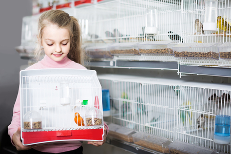 Smiling american  girl customer happy about buying cage with canary bird in pet shop