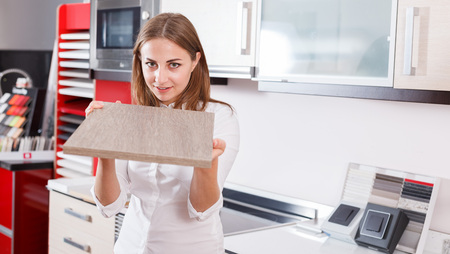 Young woman choosing material for kitchen furniture in salon Stok Fotoğraf