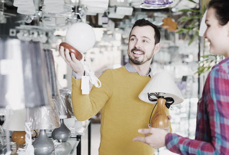 Young spanish man and girl in lighter shop choosing stylish and modern lamp for house interior