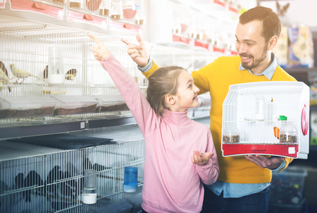 Father and daughter decide to buy a canary or parrot in the pet  store Stock Photo