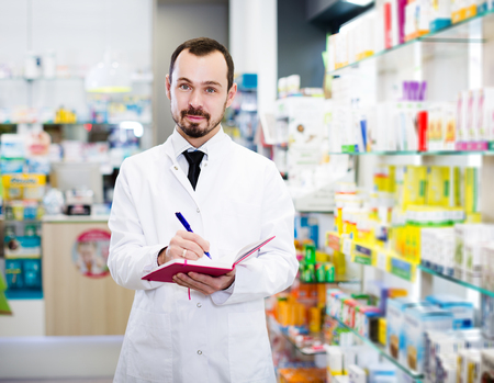 Glad adult pharmacist writing down assortment of drugs in pharmacy