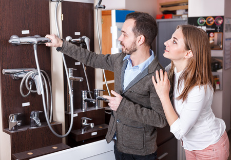 Young couple choosing new shower mixer in bathroom fixtures store. Focus on both persons