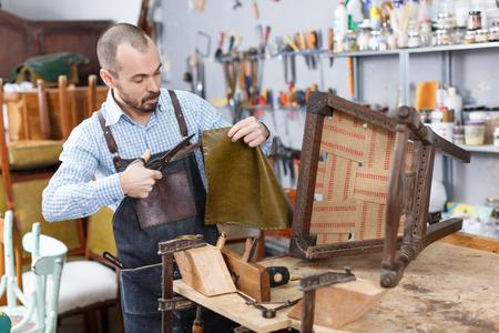 Qualified workman upholstering chair in repair furniture workshop
