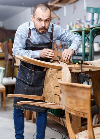 Craftsman engaged in retro chair repair in modern workshop Imagens - 117325472