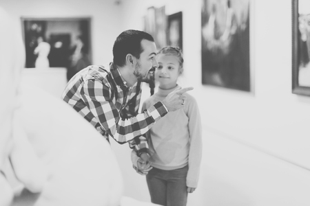 Positive adult father and daughter looking at expositions in museum