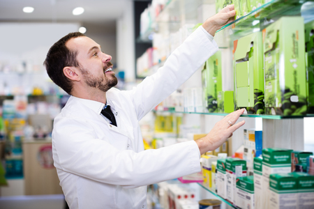Smiling man pharmacist browsing rows of drugs in drugstore Stockfoto