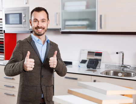 Portrait of contented bearded  cheerful positive guy in kitchen furnishing store