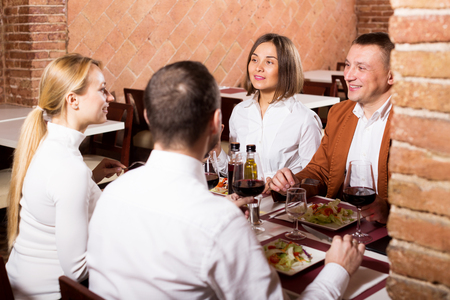 Smiling company of friends eating delicious dinner in country restaurant