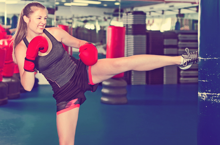 Glad cheerful positive woman boxer is training kick in box gym.