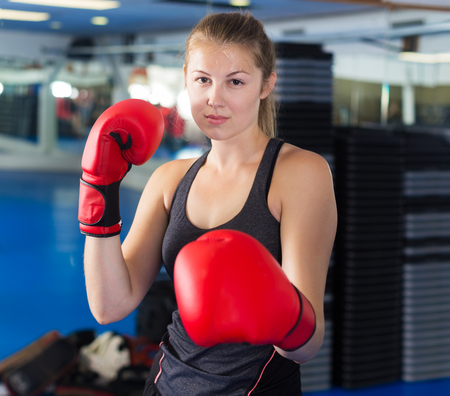 Portrait of young female in red boxing gloves training in gym