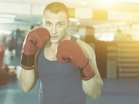 Glad cheerful positive man boxer is training in gloves in gym.