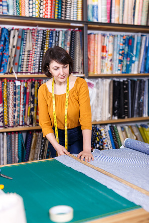 Competent saleswoman measuring ordered cloth for cutting in textile shop, preparing for sale 免版税图像