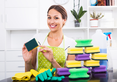 Cheerful young brunette woman wearing apron sitting with heap of cleaning sponges indoors