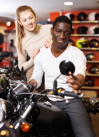 happy adult  man and woman in motorcycle shop choosing new vehicle to buy Фото со стока