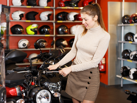 Portrait of young woman looking new motorbike at modern showroom Фото со стока - 117499083