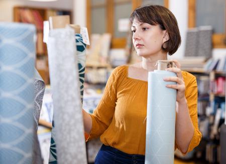 Venditore femminile che organizza assortimento di tessuti sugli scaffali nel negozio di tessuti