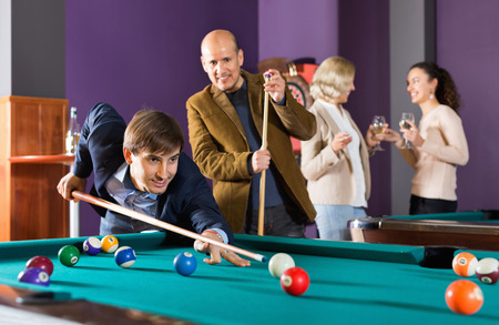 Group of happy friends playing billiards and smiling in night club