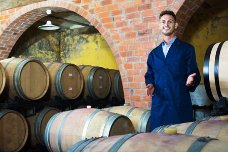 portrait of young positive male wine maker in coat working in winery cellar