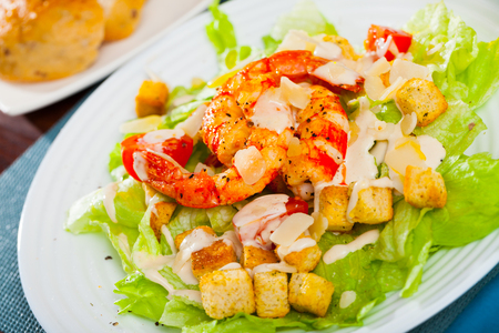 Delisiously Caesar salad with prawns, lettuce,  sauce and cheese